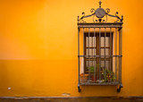 Antique medieval window with rusty iron bars and orangewall