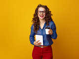 woman against yellow background with coffee cup and tablet PC