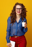 woman on yellow background with coffee cup and tablet PC