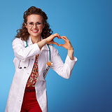 smiling paediatrist doctor showing heart shaped hands on blue