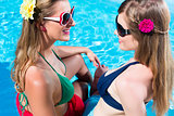 Girl friends tanning at swimming pool in front of water