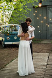 Merry happy young couple hugging near a retro bus