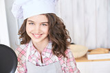 Beautiful girl. Little cook. White cap. Brown curly hair