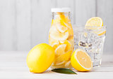 Glass bottle of lemon still fruit water