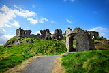 Stone castle ruins in the green grass of Ireland