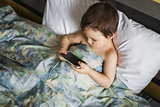 modern boy playing phone lying on the bed in morning