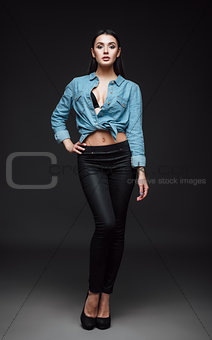 Studio fashion shot: portrait of lovely young girl in jeans and shirt
