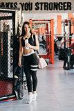 Beautiful young sportswoman in sportswear is holding a bottle of water