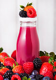 Glass bottles with fresh summer berries smoothie