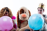 Young woman with man blowing big balloons