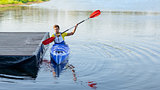 Young Professional Kayaker Paddling Kayak on River under Bright Morning Sun. Sport and Active Lifestyle Concept