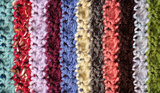 Crocheted yarn stitches in mixed colour stripes background
