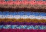 Background of crocheted stitches in multi-coloured stripes