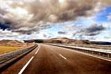 Empty highway,mountain landscape and cloudy sky.Road and car tra