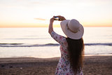 Young woman taking photo the sea and sunset with cell phone or smartphone digital camera for Post to Online Internet While travel on vacation holiday.
