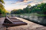 Chaise longues near river