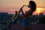 Young girl with a saxophone on the roof