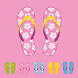 Row of colorful beach flip flops over color background