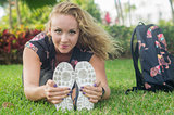 Blonde girl, does exercise sitting on the grass, stretches her body facing camera