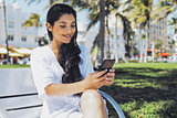 Confident stylish girl using phone in park