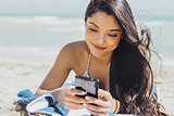 Pretty girl using phone on beach