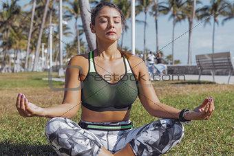 Woman meditating in green park