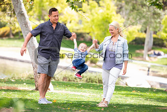 Young Mother and Father Swingging Their Son At The Park