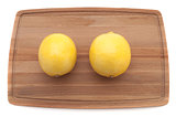 two yellow bright juicy lemon on a wooden cutting board top view