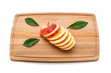 Sliced delicious luscious apple with green leaves on a cutting board made of wood.