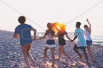 Group of happy friends having fun at ocean beach