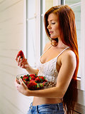 Beautiful redhead with bowl of strawberries