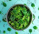 green spinach leaves in an iron colander