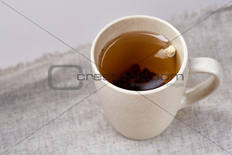 Cup of tea on table with sackcloth, top view, close-up, selective focus