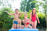 Family cooling down splashing water in garden pool