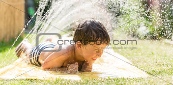 Boy cooling down with garden hose, family in the background