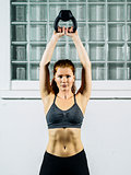 Young redhead woman exercising with a kettlebell