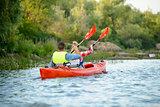 Young Happy Couple Paddling Kayak on Beautiful River or Lake