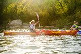 Young Happy Couple Paddling Kayaks on Beautiful River or Lake