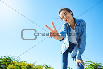 portrait of a young attractive woman on the blue sky background
