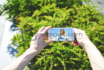 portrait of a young attractive woman using mobile phone on the blue sky background