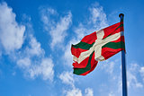 Ikurrina, Basque Country flag waving on a blue sky.