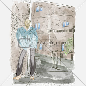 A guy poses against the background of an old house