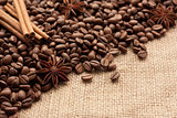 Roasted coffee beans are scattered on sackcloth with star anise and cinnamon sticks.
