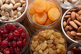 Nuts and dried fruits assortment in jars and bowls.