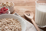 Oatmeal with dried cherries, cashews, milk and a wooden spoon on wooden table.