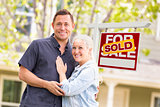 Caucasian Couple in Front of Sold Real Estate Sign and House