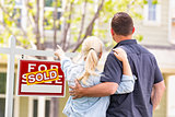 Caucasian Couple Facing and Pointing to Front of Sold Real Estat