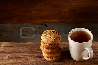 White porcelain mug of tea and sweet cookies on piece of wood over wooden background, top view, selective focus