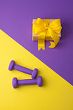 Sport flat lay composition with dumbbells and gift box