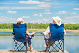 view from the back of a couple on chairs relaxes near a lake on